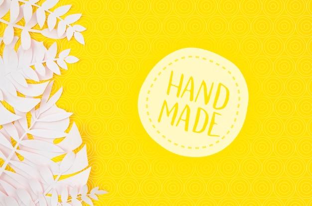 Значок ручной работы с белыми листьями на желтом фоне Бесплатные Psd