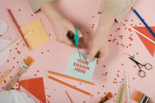 Mani che tagliano una carta con il logo del tuo design Psd Gratuite