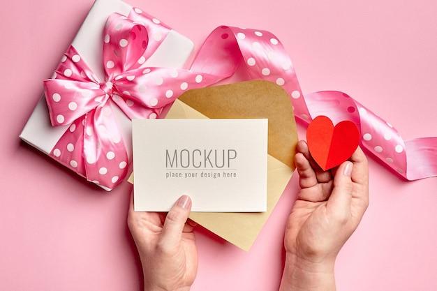 선물 상자와 종이 마음으로 발렌타인 데이 카드 모형을 들고 손 프리미엄 PSD 파일