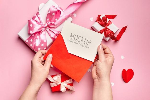 선물 상자와 함께 발렌타인 카드 모형을 들고 손 프리미엄 PSD 파일