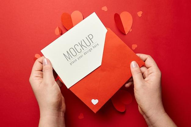 종이 마음으로 발렌타인 데이 카드 모형을 들고 손 프리미엄 PSD 파일