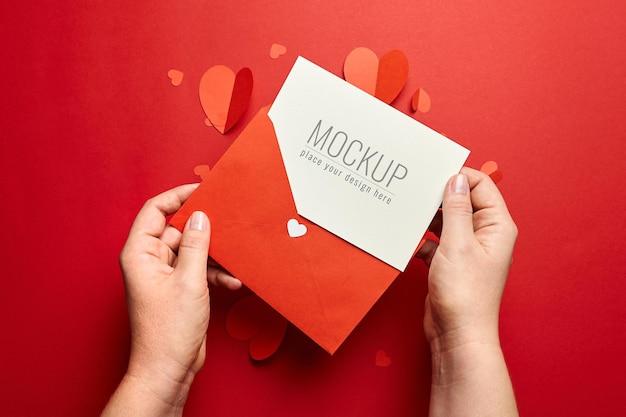 빨간색 종이 마음으로 발렌타인 데이 카드 모형을 들고 손 프리미엄 PSD 파일