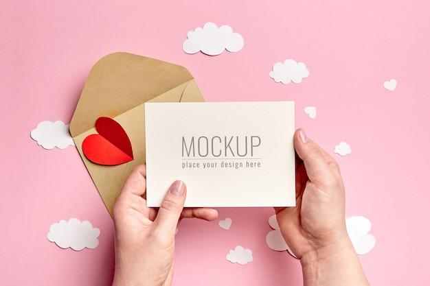 분홍색에 종이 구름과 하트와 Valrntines 하루 카드 모형을 들고 손 프리미엄 PSD 파일
