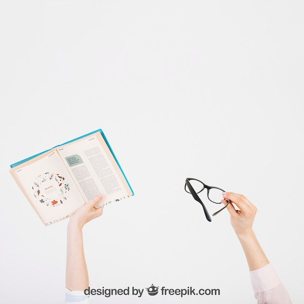 Hands raising book and glasses Free Psd