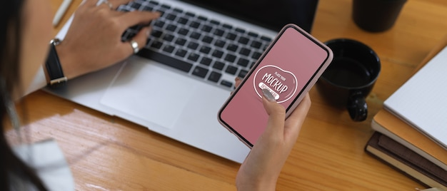 Руки пишут текстовые сообщения на макете смартфона во время работы с ноутбуком Premium Psd