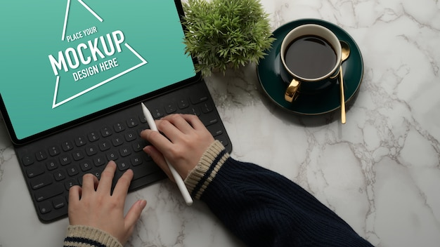 Hands typing on mock up digital tablet on marble desk with coffee cup and plant pot Premium Psd