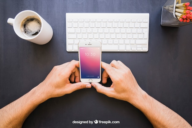 Hands with phone and office desk Free Psd