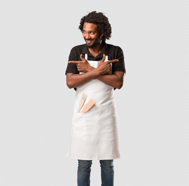 Handsome african american baker confused and doubtful man, decide between two options, concept of indecision Premium Psd