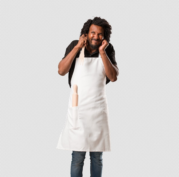 Handsome african american baker covering ears with hands, angry and tired of hearing some sound Premium Psd