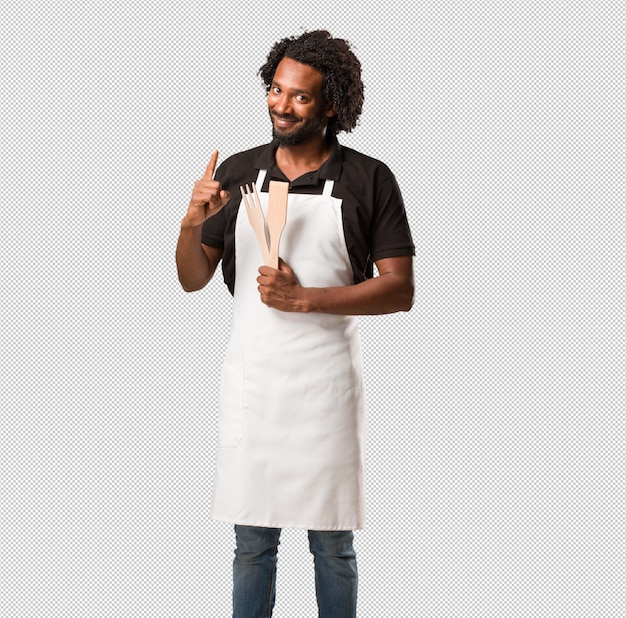 Handsome african american baker showing number one, symbol of counting,  mathematics, confident and cheerful Premium Psd