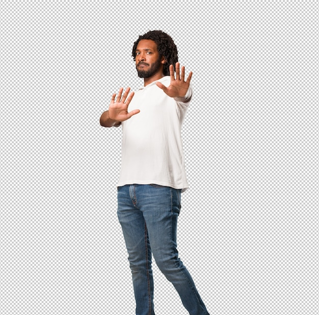 Handsome african american serious and determined, putting hand in front, stop gesture, deny Premium Psd