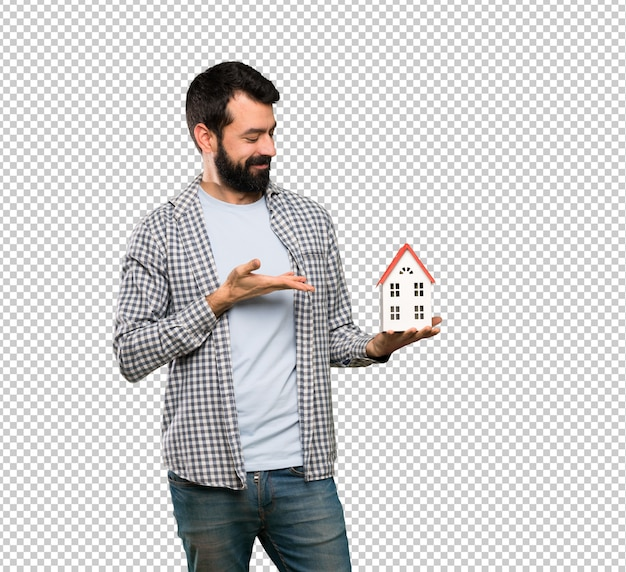 Handsome man with beard holding a little house Premium Psd