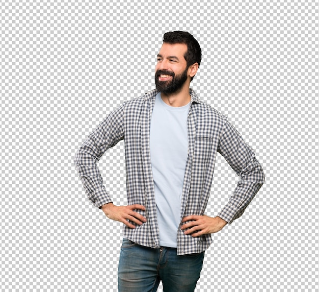 Handsome man with beard posing with arms at hip and smiling Premium Psd