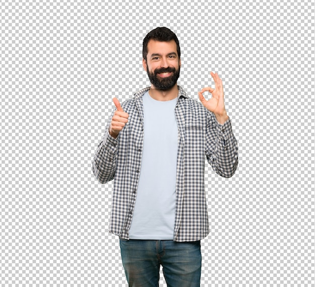 Handsome man with beard showing ok sign and thumb up gesture Premium Psd