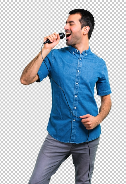Handsome man with blue shirt singing with microphone Premium Psd