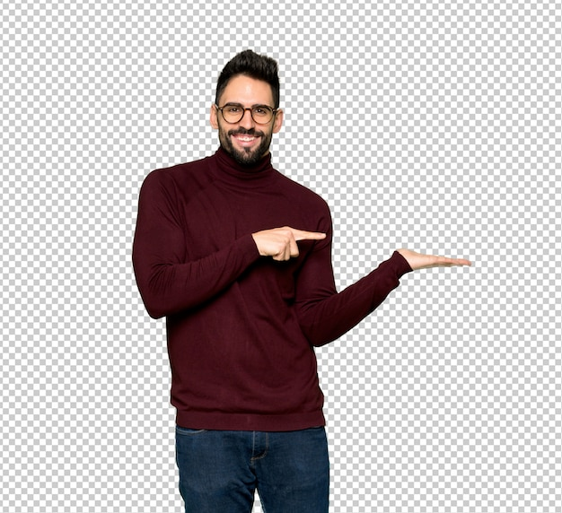 Handsome man with glasses holding copyspace imaginary on the palm to insert an ad Premium Psd