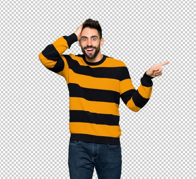 Handsome man with striped sweater pointing finger to the side and presenting a product Premium Psd
