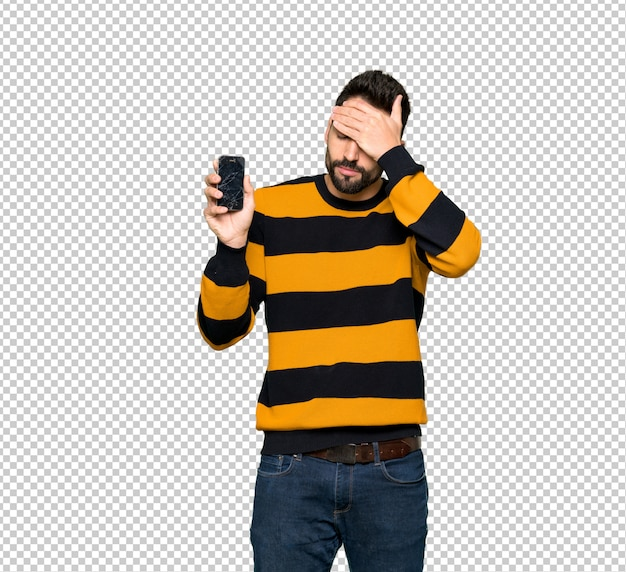 Handsome man with striped sweater with troubled holding broken smartphone Premium Psd