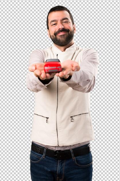 Handsome man with vest holding a little car Premium Psd