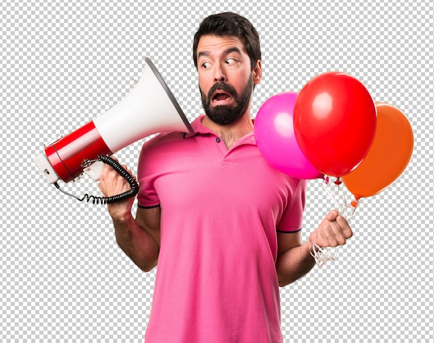 Handsome young man holding balloons and  holding a megaphone Premium Psd
