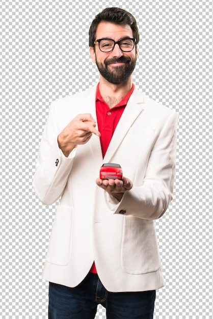 Happy brunette man with glasses holding little car Premium Psd