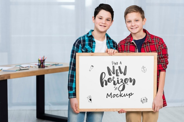 Happy children holding mock-up sign Free Psd
