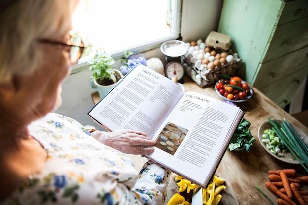 Happy elderly woman reading a cookbook Premium Psd