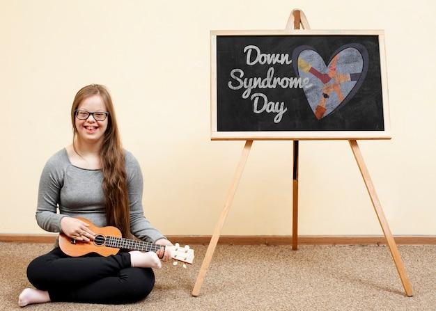 Счастливая девушка с синдромом дауна играет укулеле с макетом у доски Бесплатные Psd
