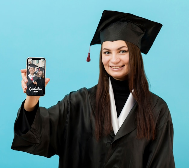 Happy graduation student holding mobile phone Free Psd
