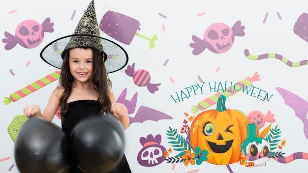 Happy halloween girl holding black balloons Free Psd