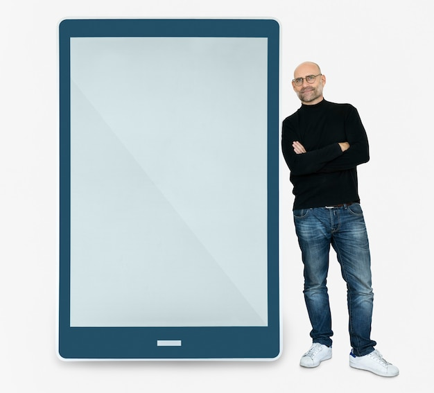 Happy man standing beside a tablet Free Psd