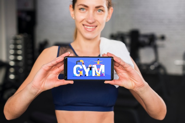 Happy sporty woman presenting smartphone mockup Free Psd