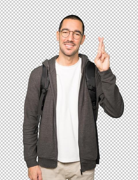 Счастливый студент делает жест скрещенными пальцами Premium Psd