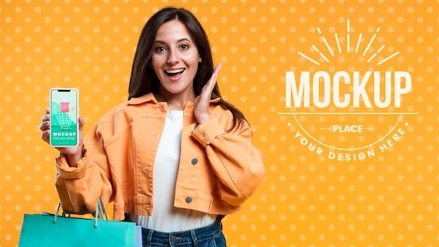 Счастливая женщина, держащая хозяйственные сумки и телефонный макет Бесплатные Psd