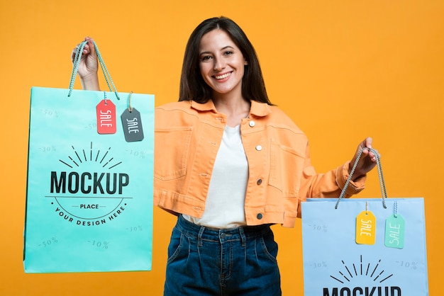 Happy woman holding shopping bags with tags mock-up Free Psd