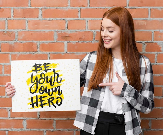 Happy woman pointing at mock-up Free Psd
