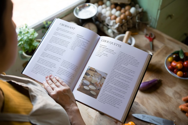 Happy woman reading a cookbook in the kitchen Premium Psd