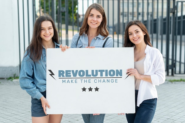 Happy women holding board with mock-up Free Psd