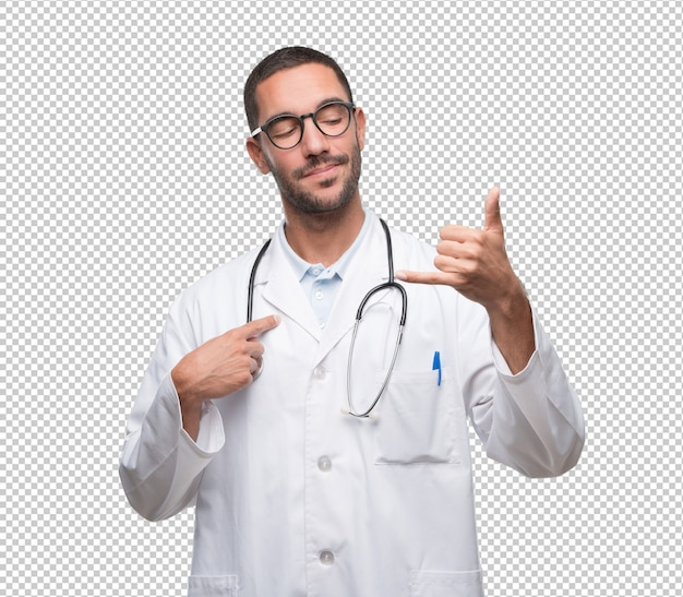 Happy young doctor doing a gesture of calling with the hand Premium Psd