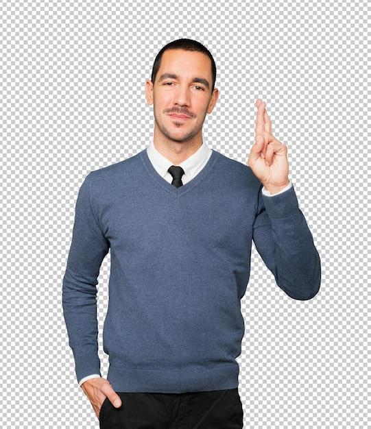 Счастливый молодой человек делает жест скрещенными пальцами Premium Psd