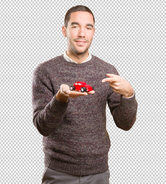 Happy young man holding a toy car Premium Psd
