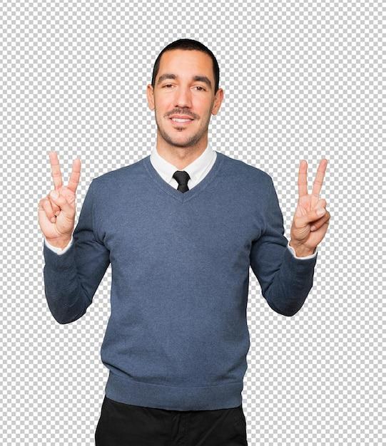Счастливый молодой человек, делая жест победы пальцами Premium Psd
