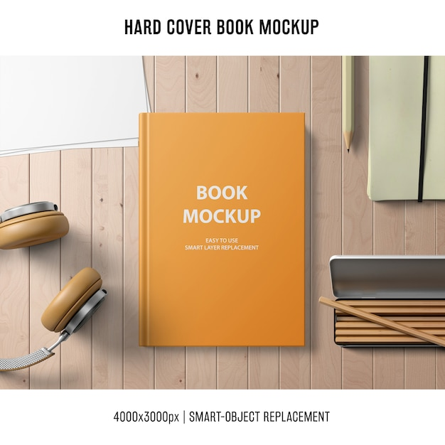 Hard cover book mockup with headphones and pencils Free Psd