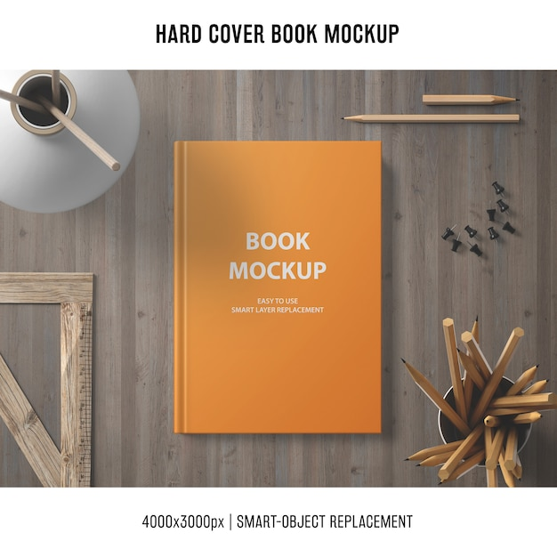 Hard cover book mockup with wooden elements Free Psd