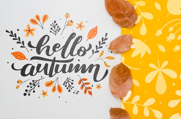 Hello autumn lettering next to yellow leaves pattern Free Psd