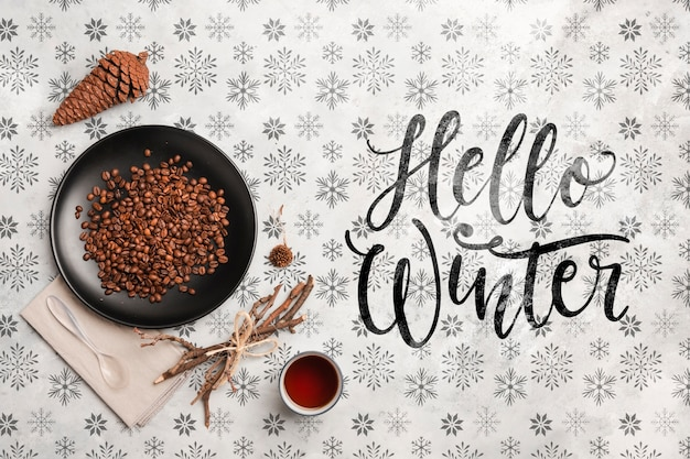 Hello winter message and coffee on table Free Psd