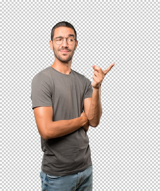 Hesitant young man pointing at you with his finger Premium Psd