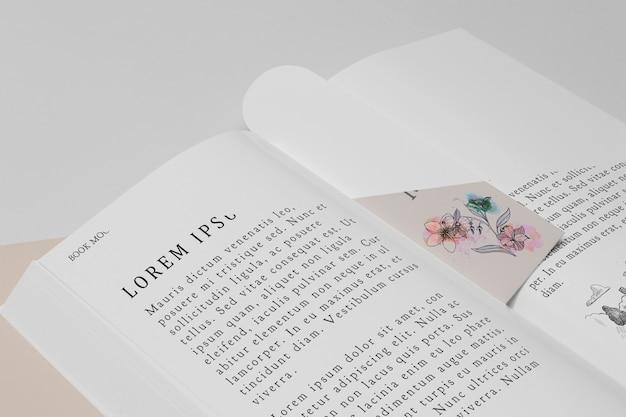 高角度の花のブックマークと開いた本のモックアップ 無料 Psd