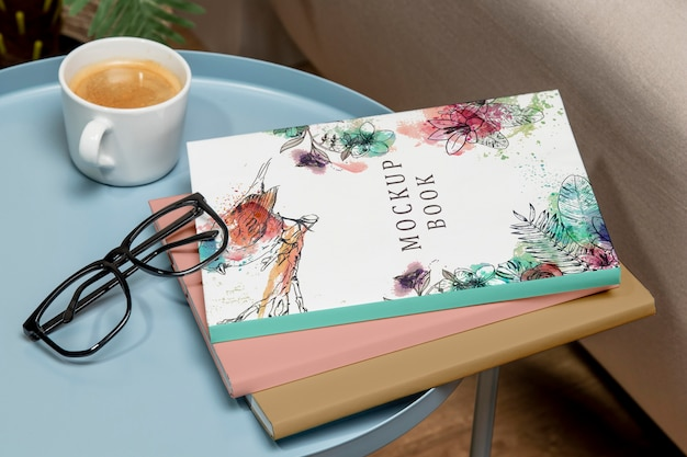 High angle stack of books mock-up on coffee table with glasses Free Psd