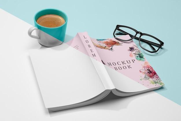 ハイアングルはメガネとコーヒーで開いた本のモックアップをひっくり返しました 無料 Psd